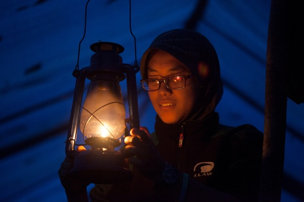 Ririn lights a lantern in camp.