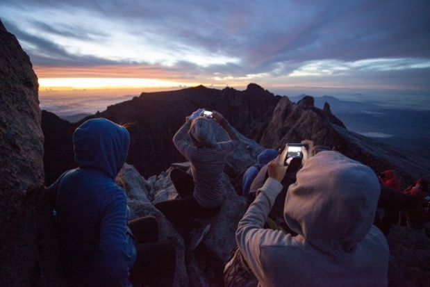 Climbers photograph sunrise from the peak.